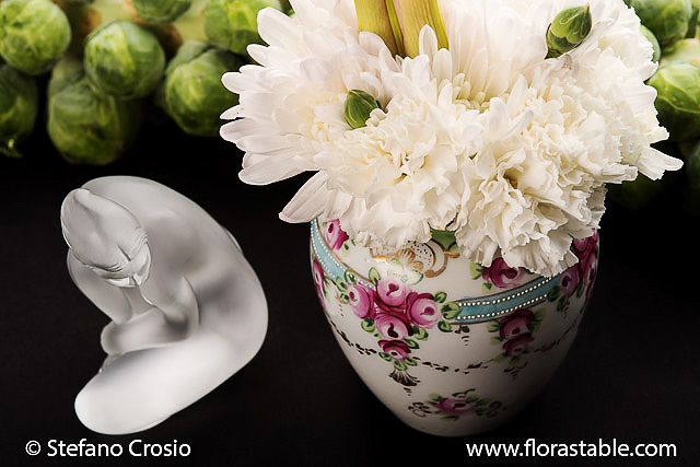 Glass statuette and flower composition with Brussel sprout backdrop